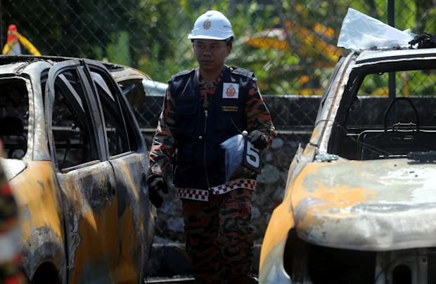 A personnel from the Fire Dept forensic taem inspects the vehicles that were burnt in an arson attack at the Kuala Kangsar Road Transport Dept office February 6, 2018. — Picture by Farhan Najib