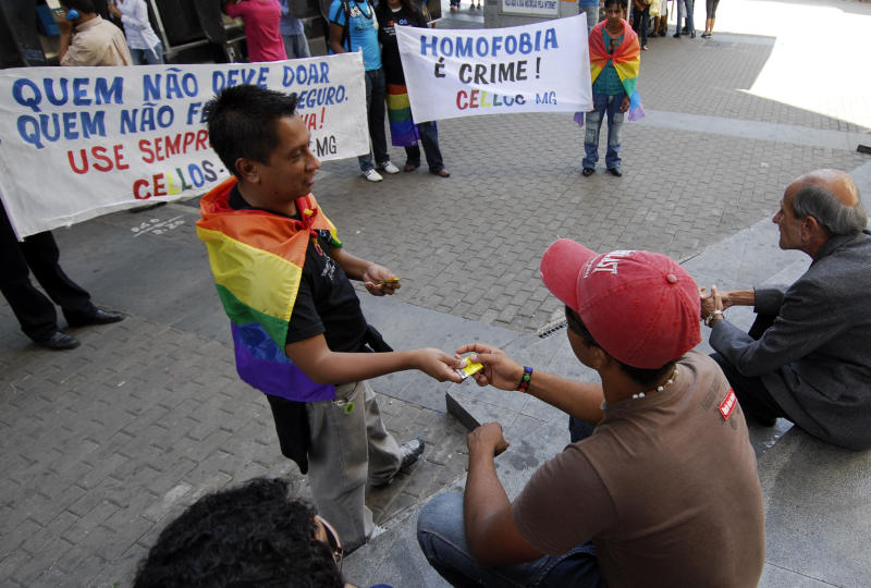 """Gay activists hold a demonstration and distribute condoms to pedestrians in downtown Belo Horizonte May 12, 2007. Gay organizations around Brazil are holding a series of protests this week to coincide with the visit by Pope Benedict XVI to Sao Paulo and the Aparecida sanctuary. The banners read, """"Those that shouldn't donate (blood) are those that didn't practice safe sex,"""" and """"Homophobia is a crime."""" REUTERS/Washington Alves (BRAZIL)"""