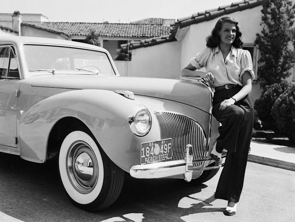 <p>Rita Hayworth poses beside an automobile in high-waisted trousers and a rolled-up shirt. </p>