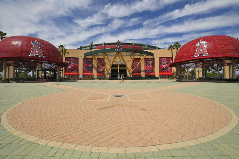 People walk by the front of Angel Stadium, Thursday, June 25, 2020, in Anaheim, Calif. By the time Major League Baseball returns in late July, it will have been more than four months since teams last played. The season is now going to be a 60-game sprint to the finish, held in ballparks without fans and featuring some unusual rules. (AP Photo/Mark J. Terrill)
