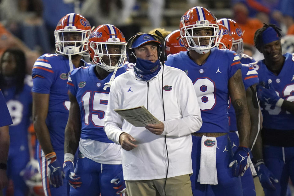 Florida head coach Dan Mullen, center, with player during a timeout in the first half of an NCAA college football game against LSU, Saturday, Dec. 12, 2020, in Gainesville, Fla. (AP Photo/John Raoux)