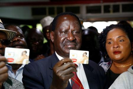 Kenyan opposition leader Raila Odinga of the National Super Alliance coalition holds a new sim card at an Airtel telecommunications shop as part of his party's campaign to boycott three big companies, including telecoms giant Safaricom, in Nairobi, Kenya November 6, 2017. REUTERS/Baz Ratner