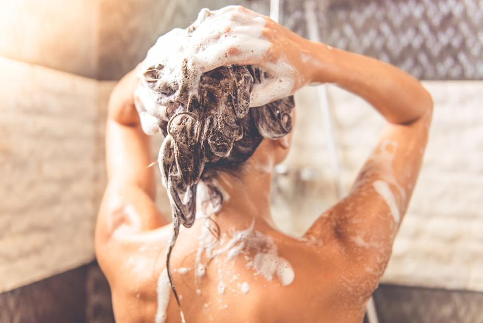 Back view of woman washing her hair in the shower