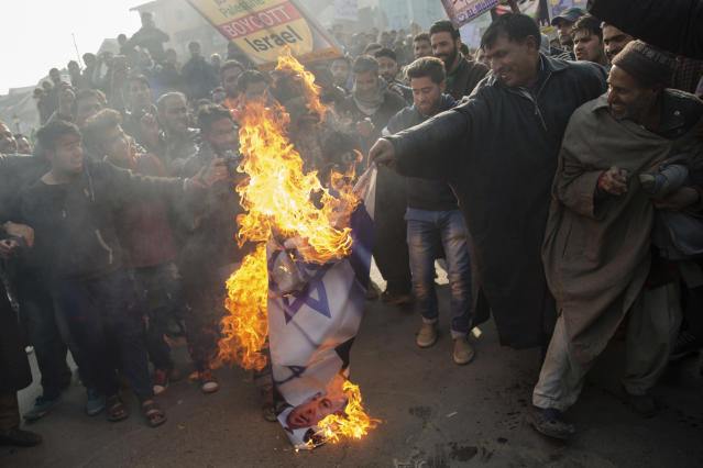 <p>Kashmiri Muslim men burn Israeli and U.S. flags during a protest against President Donald Trump's decision to recognize Jerusalem as Israel's capital in Budgam, southwest of Srinagar, Indian controlled Kashmir, Friday, Dec. 8, 2017.. (Photo: Dar Yasin/AP) </p>