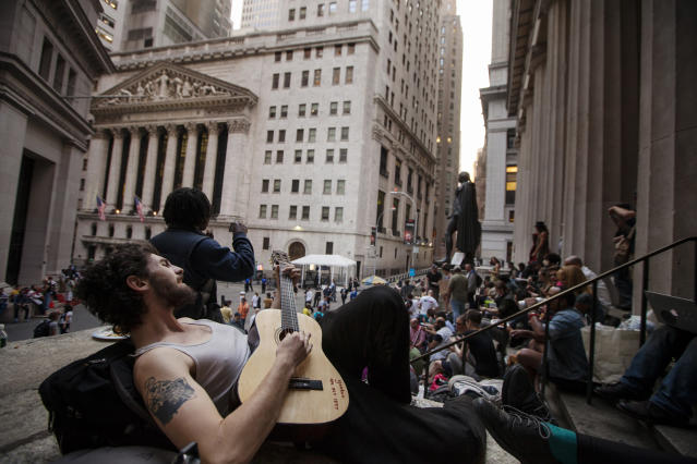 A member of the Occupy movement plays his guitar while resting on the steps of Federal Hall near the New York Stock Exchange in New York, April 16, 2012. REUTERS/Lucas Jackson