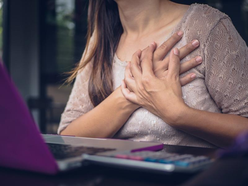 Woman touching breast and having chest pain after long hours work on computer
