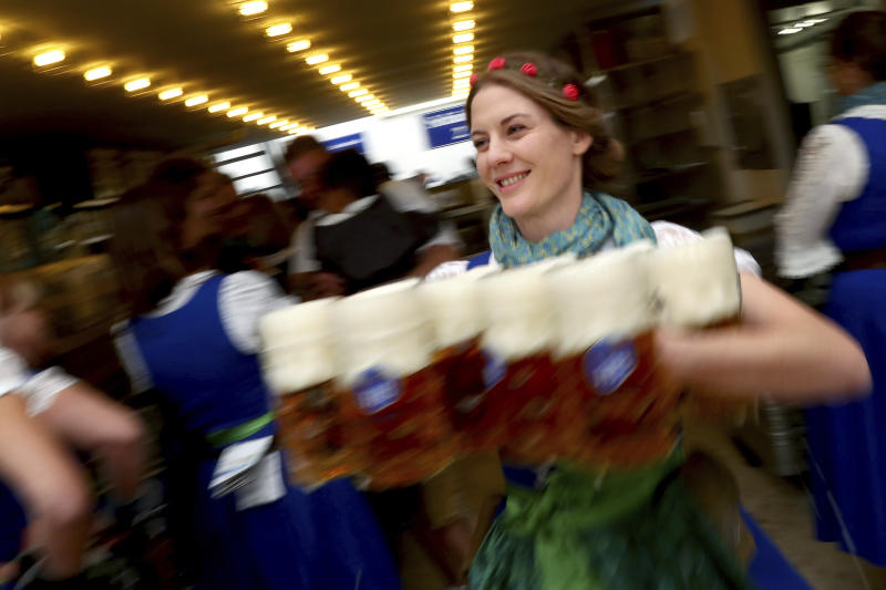 A waitress holds glasses of beer during the opening of the 186th 'Oktoberfest' beer festival in Munich, Germany, Saturday, Sept. 21, 2019. (AP Photo/Matthias Schrader)