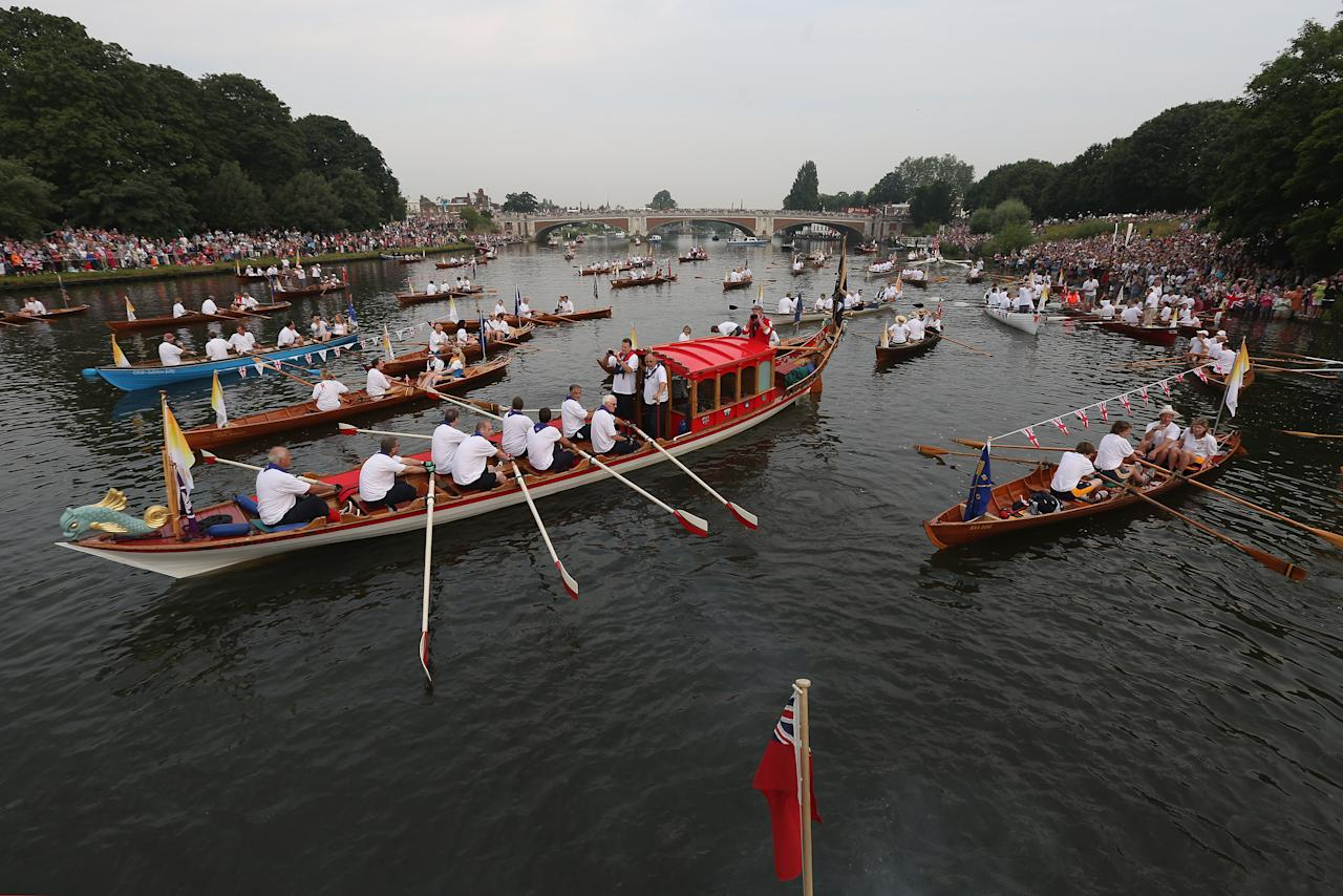 LONDON, ENGLAND - JULY 27:  A flotilla of boats accompanies the Queen's rowbarge 'Gloriana' carries the Olympic flame along the river Thames from Hampton Court to City Hall on the final day of the London 2012 Olympic Torch Relay on July 27, 2012 in London, England. The Olympic flame is making its way through the capital on the final day of its journey around the UK before arriving in the Olympic Stadium tonight for the Olympic games' Opening Ceremony.  (Photo by Oli Scarff/Getty Images)