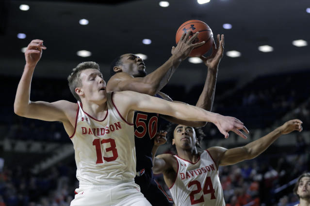 Auburn center Austin Wiley (50) goes up to collect an offensive rebound against Davidson guard Mike Jones (13) and guard Carter Collins (24) during the first half of an NCAA college basketball game at the Veterans Classic Tournament, Friday, Nov. 8, 2019, in Annapolis, Md. (AP Photo/Julio Cortez)