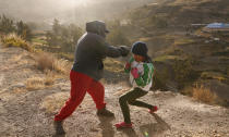 Gracce Kelly Flores trains under the coaching of her father Alberto Flores in Palca, Bolivia, early Thursday, June 10, 2021, amid the COVID-19 pandemic. At age 8, Flores defeated a 10-year-old boy, and with three national boxing medals under her belt, she dreams of reaching the women's boxing world championship. (AP Photo/Juan Karita)