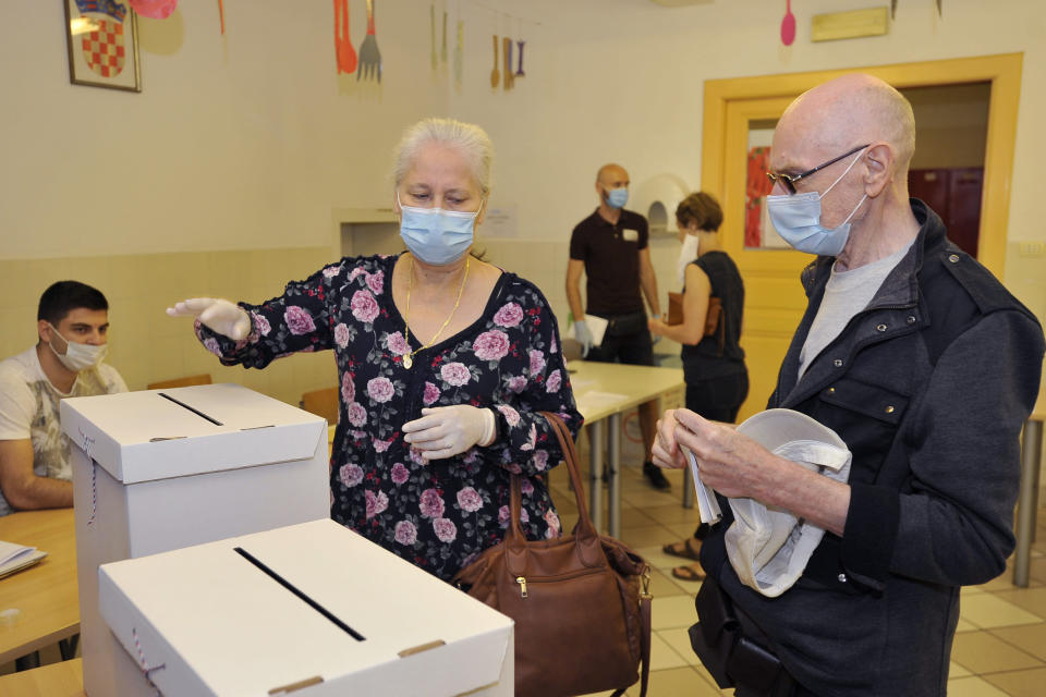 Voters casts ballots at a polling station in Zagreb, Croatia, Sunday, July 5, 2020. Amid a spike of new coronavirus cases, voters in Croatia cast ballots on Sunday in what is expected be a close parliamentary race that could push the latest European Union member state further to the right. (AP Photo)