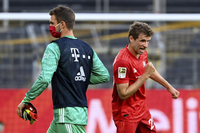 Munich's goalkeeper Sven Ulreich, left, and Munich's Thomas Mueller, right, celebrate after the German Bundesliga soccer match between Borussia Dortmund and FC Bayern Munich in Dortmund, Germany, Tuesday, May 26, 2020. The German Bundesliga is the world's first major soccer league to resume after a two-month suspension because of the coronavirus pandemic. (Federico Gambarini/DPA via AP, Pool)