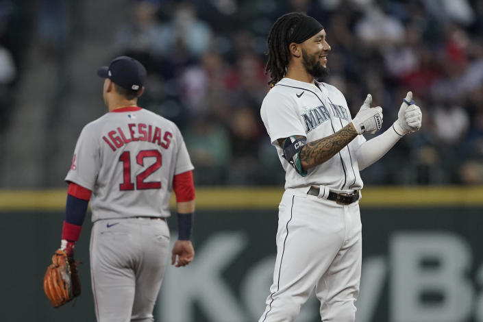Seattle Mariners' J.P. Crawford, right, reacts next to Boston Red Sox second baseman Jose Iglesias (12) after Crawford hit a double, with fan interference, during the first inning of a baseball game, Monday, Sept. 13, 2021, in Seattle. (AP Photo/Ted S. Warren)