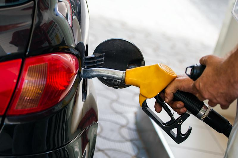 Pumping gas at gas pump. Closeup of man pumping gasoline fuel in car at gas station. Man's hand refueling car at gas station