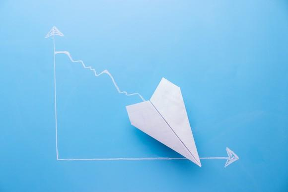 White paper airplane pointing about 45 degree downward on a blue graph background.