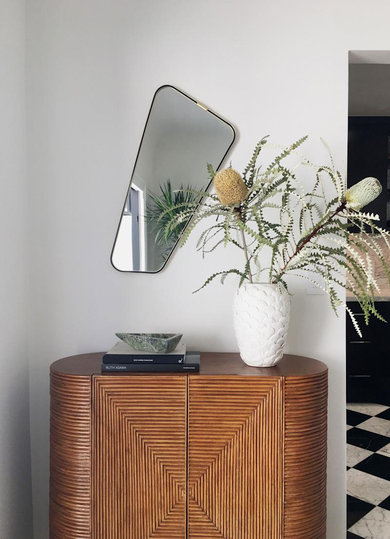 """""""One of my favorite pieces is this vintage brass framed piece from the 1960s via Vinovo, a shop in Germany,"""" says Alice, referring to the mirror. """"I loved that it was interesting and unique—the asymmetry added a subtle unexpected punch to the space."""" The console is a piece Georgia found from CB2. """"It worked really well in the space amidst all the vintage pieces we acquired."""""""