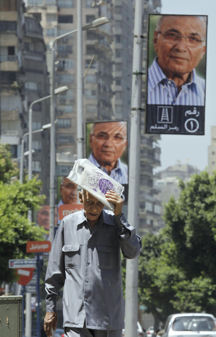 "An Egyptian walks past posters supporting Egyptian presidential candidate Ahmed Shafiq in Cairo, Egypt, Monday, June 11, 2012. Shafiq, the last prime minister of deposed president Hosni Mubarak, will face the Muslim Brotherhood's candidate, Mohammed Morsi, in a run-off on June 16-17. Arabic reads, ""number 1, symbol ladder."" (AP Photo/Amr Nabil)"