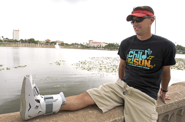 In this photo taken Thursday, April 19, 2012, Greg Farris takes a break while wearing a protective boot as he helps set up for a weekend triathlon event in Lakeland, Fla. Farris injured his foot while running in barefoot running shoes.(AP Photo/John Raoux)