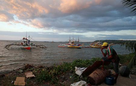 A fisherman look at the fishing boats that just returned from disputed Scarborough Shoal, as they are docked at the coastal village of Cato in Infanta, Pangasinan in the Philippines, October 31, 2016. REUTERS/Erik De Castro