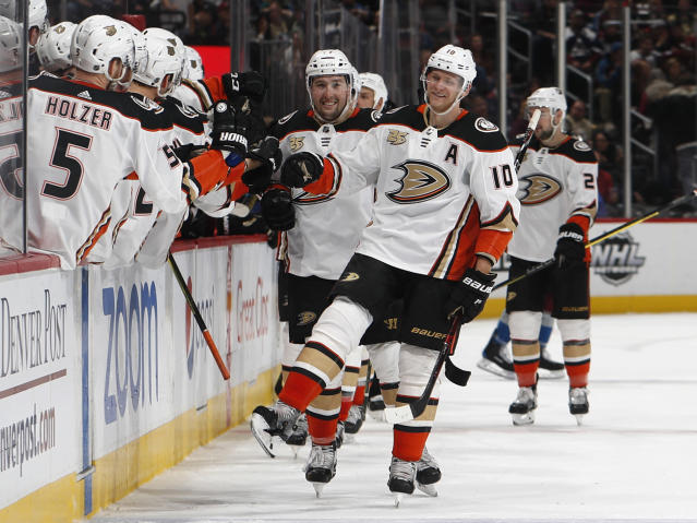"FILE - In this March 15, 2019, file photo, Anaheim Ducks right wing Corey Perry, right, is congratulated as he passes the team box after scoring the go-ahead goal against the Colorado Avalanche during the third period of an NHL hockey game, in Denver. The Anaheim Ducks have bought out the contract of former NHL MVP Corey Perry after 14 seasons with the franchise. The Ducks announced the move Wednesday, June 19, 2019. General manager Bob Murray called it ""one of the most difficult decisions I've had to make in my 44 years in the NHL."" (AP Photo/David Zalubowski, File)"