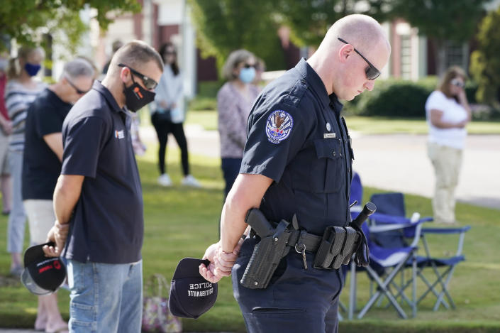 Officer Ben Hubbard, of the Collierville Police Department, prays during a vigil at the Collierville Town Hall, Friday, Sept. 24, 2021, in Collierville, Tenn. The vigil is for the person killed and those injured when a gunman attacked people in a Kroger grocery store Thursday before he was found dead of an apparent self-inflicted gunshot wound. (AP Photo/Mark Humphrey)