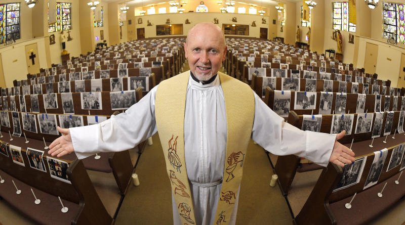 FILE - In this May 22, 2020, file photo, the Rev. Nicolas Sanchez Toledano poses among pews adorned with portraits of his parishioners at St. Patrick's Catholic Church during the coronavirus outbreak in the North Hollywood section of Los Angeles. California says churches can resume in-person services but the congregations will be limited to less than 100 and worshippers should wear masks, avoid sharing prayer books and skip the collection plate. The state Department of Public Health released a framework Monday, May 25, for county health officials to permit houses of worship to reopen.  (AP Photo/Mark J. Terrill, File)
