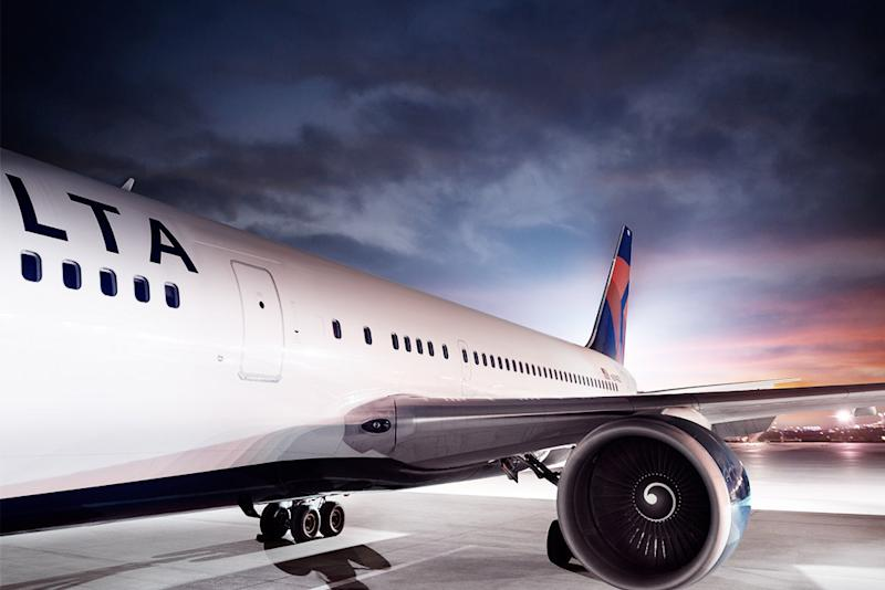 Delta-labeled aircraft on white flooring under a dark sky near sunset.