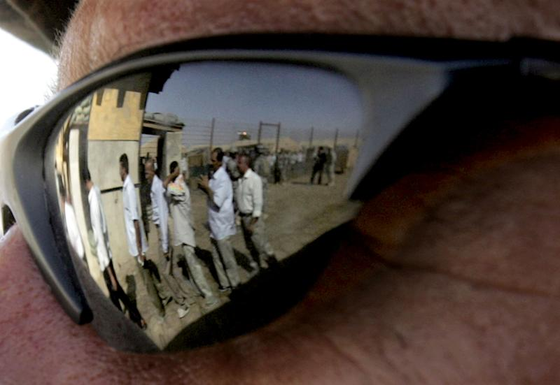 Iraqis leaving the prison are reflected in the sunglasses of a US soldier at the Abu Ghraib prison, west of Baghdad, June 27, 2006