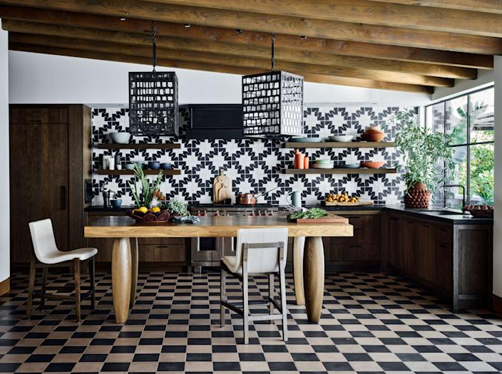 """Black-and-white patterned tiles from Mosaicos Oaxaca, along with checkerboard cement tiles, help set the bold yet casual style of the kitchen. The 36-inch-tall table, which is used for snacking and working, was custom made. The hanging lanterns are from <a href=""""https://gregoriuspineo.com"""" rel=""""nofollow noopener"""" target=""""_blank"""" data-ylk=""""slk:Gregorius Pineo"""" class=""""link rapid-noclick-resp"""">Gregorius Pineo</a>."""