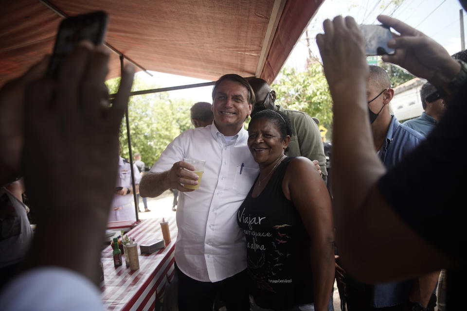 """Brazil's President Jair Bolsonaro, left, poses for a photo with a supporter after voting during run-off municipal elections in Rio de Janeiro, Brazil, Sunday, Nov. 29, 2020. Bolsonaro, who sometimes has embraced the label """"Trump of the Tropics,"""" said Sunday he'll wait a little longer before recognizing the U.S. election victory of Joe Biden, while echoing President Donald Trump's allegations of irregularities in the U.S. vote. (AP Photo/Silvia Izquierdo)"""