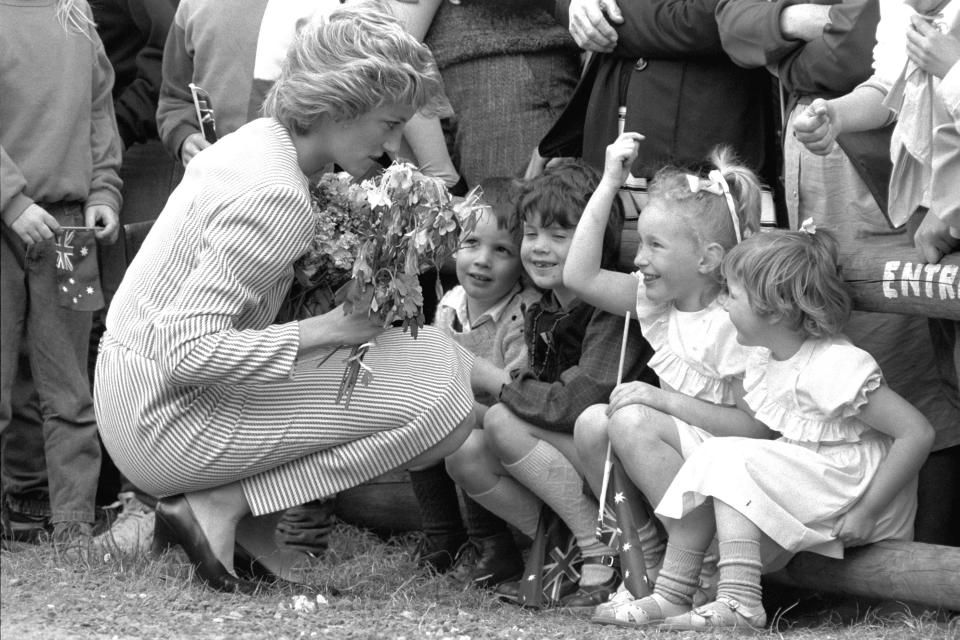 """FILE - In this file photo dated Feb. 11, 1985, Britain's Princess Diana stoops to speak to children during a visit to Macedon, Australia. For someone who began her life in the spotlight as """"Shy Di,"""" Princess Diana became an unlikely, revolutionary during her years in the House of Windsor. She helped modernize the monarchy by making it more personal, changing the way the royal family related to people. By interacting more intimately with the public -- kneeling to the level of children, sitting on edge of a patient's hospital bed, writing personal notes to her fans -- she set an example that has been followed by other royals as the monarchy worked to become more human and remain relevant in the 21st century. (AP Photo / Jim Bourdier, File)"""