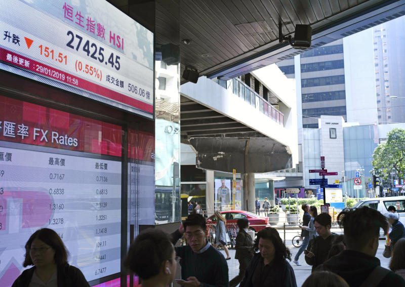 People walk past an electronic board showing Hong Kong share index outside a local bank in Hong Kong, Tuesday, Jan. 29, 2019. Asian markets were lower on Tuesday after the U.S. Justice Department unsealed criminal charges against China's Huawei, its subsidiaries and a top executive ahead of trade talks. (AP Photo/Vincent Yu)
