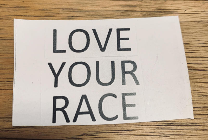 "A sign that read ""LOVE YOUR RACE"" was posted outside on the store front of a local business called Broomstick Betty. (Credit: Jacqueline Laven)"
