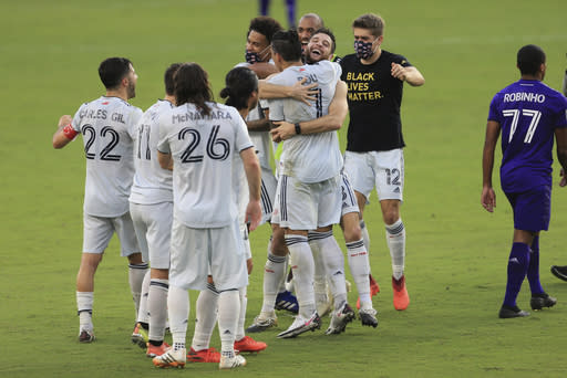 New England Revolution players celebrate after an MLS playoff soccer match against Orlando City, Sunday, Nov. 29, 2020, in Orlando, Fla. (AP Photo/Matt Stamey)