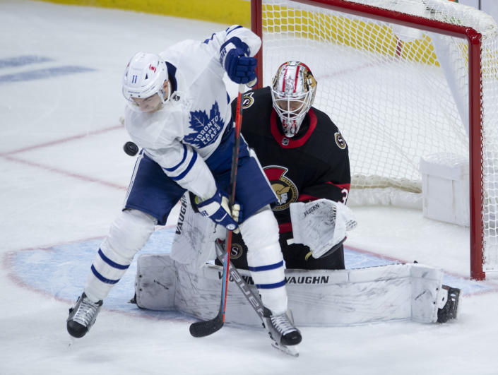 Toronto Maple Leafs left wing Zach Hyman (11) screens Ottawa Senators goaltender Matt Murray on a shot during the second period of an NHL hockey game in Ottawa, Ontario, Saturday, Jan. 16, 2021. (Adrian Wyld/The Canadian Press via AP)