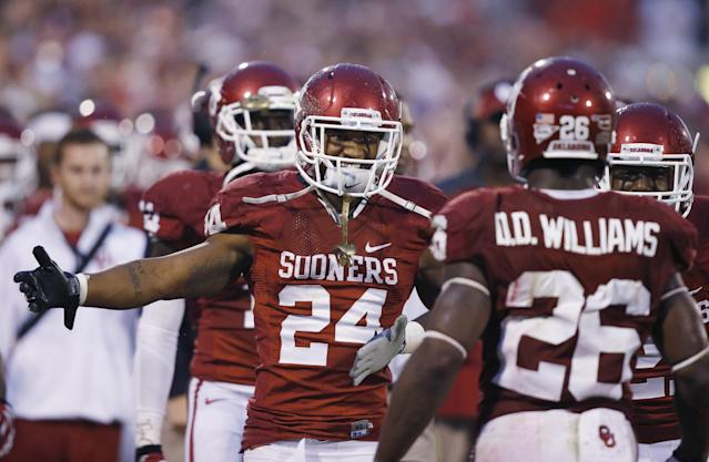Oklahoma running back Brennan Clay (24) greets teammate Damien Williams (26) on the sidelines after Williams scored a touchdown against Texas Tech in the fourth quarter of an NCAA college football game in Norman, Okla., Saturday, Oct. 26, 2013. Oklahoma won 38-30. (AP Photo/Sue Ogrocki)