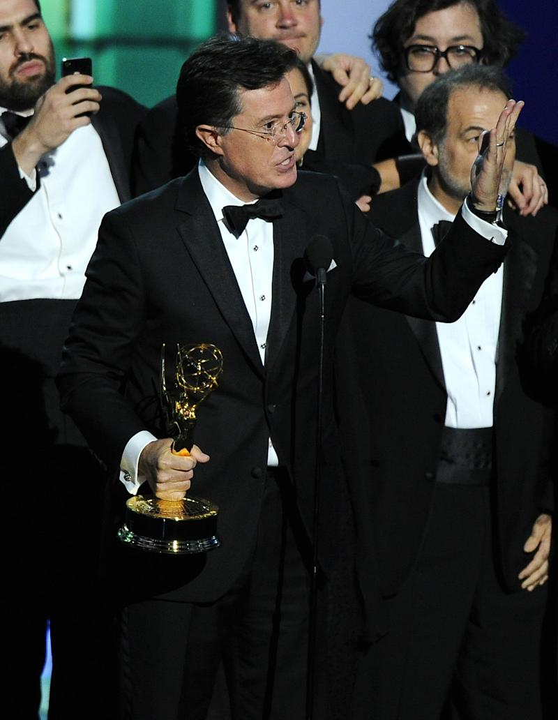"""Stephen Colbert and the cast and crew of """"The Colbert Report"""" accept the award for outstanding writing for a variety series at the 65th Primetime Emmy Awards at Nokia Theatre on Sunday Sept. 22, 2013, in Los Angeles. (Photo by Chris Pizzello/Invision/AP)"""