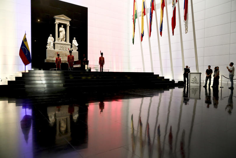 People walk inside the Mausoleum that contains the remains of independence hero Simon Bolivar in Caracas, Venezuela, Wednesday, March 6, 2019. Simon Bolivar was a Venezuelan military and political leader who led the secession of what are currently the states of Venezuela, Bolivia, Colombia, Ecuador, Peru, and Panama from the Spanish Empire. (AP Photo/Eduardo Verdugo)