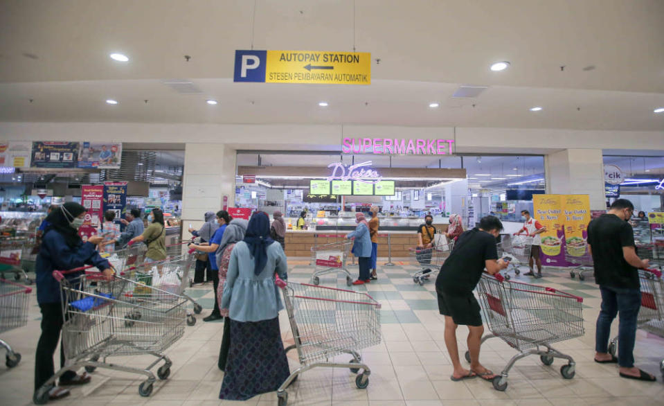 Customers queuing up with the trollies at the Aeon Kinta City supermarket in Ipoh to stock up their supplies as government announced enhanced movement control order (EMCO) May 21, 2021. — Picture by Farhan Najib