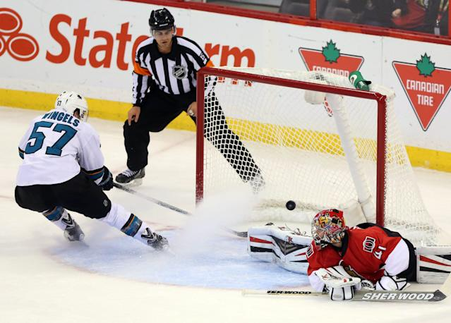 San Jose Sharks' Tommy Wingels (57) scores a short-handed goal against Ottawa Senators goaltender Craig Anderson, right, during first-period NHL hockey game action in Ottawa, Ontario, Sunday, Oct. 27, 2013. (AP Photo/The Canadian Press, Fred Chartrand)