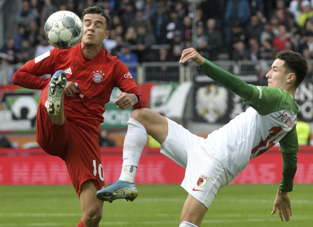 Augsburgs Ruben Vargas, right, and Munich's Philippe Coutinho challenge for the ball during a German Bundesliga soccer match between FC Augsburg and Bayern Munich in Augsburg, Germany, Saturday, Oct.19, 2019. (Stefan Puchner/dpa via AP)