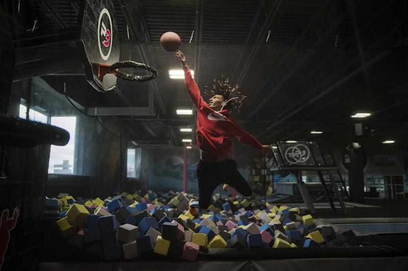 Taevion Rushing flies to the basket as he and his Flint teammates play at a local trampoline park during a snow day.