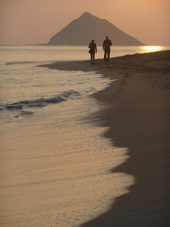 FILE - In this file photo from Monday, Jan. 25, 2010, a couple walks along the water's edge at Lanikai Beach in the haze of heavy 'vog' giving the sky, ocean and sunrise pink and yellow hue in Kailua, Hawaii. Part of what makes living in Hawaii so pleasant is the gentle breezes. Nowadays, these breezes, called trade winds, are declining, a drop that's slowly changing life across the islands. (AP Photo/Lucy Pemoni)