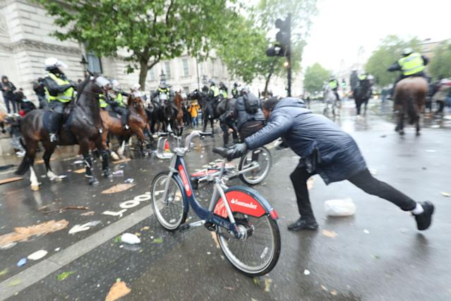 A public hire bicycle is thrown at mounted police on horseback in Whitehall following a Black Lives Matter protest rally in Parliament Square, London on Saturday (PA)