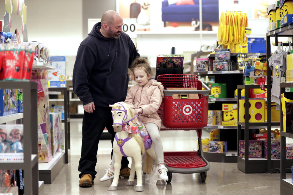 In this Friday, Nov. 16, 2018, photo James Deakyne, left, looks at items in his cart as his 7-year-old daughter, Madison, sits on a toy horse during a trip to get toys for her birthday at a Target store in Edison, N.J. Companies from Target to online mattress company Casper aren't just counting on a stronger economy to pump up sales. Target's CEO Brian Cornell estimated last month there's up to $100 billion in market share for grabs, double what he foresaw just a year ago. So Target is accelerating its store remodels in areas where bankrupt retailers had stores. (AP Photo/Julio Cortez)