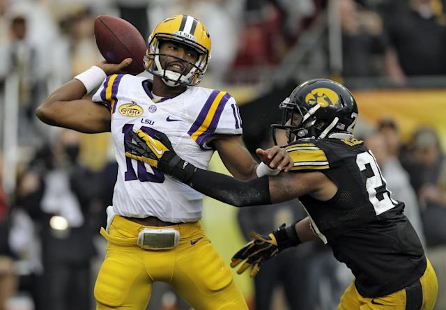 LSU quarterback Anthony Jennings (10) throws a pass as he gets hit by Iowa linebacker Christian Kirksey (20) during the first quarter of the Outback Bowl NCAA college football game Wednesday, Jan. 1, 2014, in Tampa, Fla. (AP Photo/Chris O'Meara)