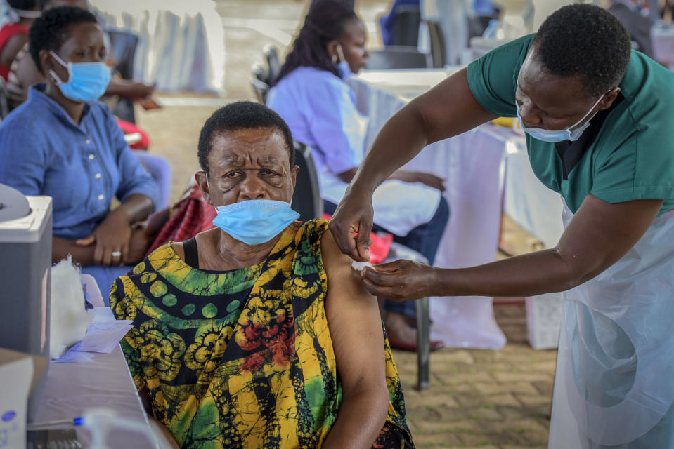 A woman receives a coronavirus vaccination at the Kololo airstrip in Kampala, Uganda, Monday, May 31, 2021. Africa is especially vulnerable. As virus cases surge in the world's poorest countries, a sense of dread is growing among millions of the unvaccinated, especially those who toil in the informal, off-the-books economy, live hand-to-mouth and pay cash in health emergencies. (AP Photo/Nicholas Bamulanzeki)