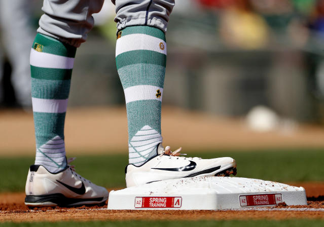 San Diego Padres' Christian Villanueva wears St. Patrick's Day themed socks during the first inning of a spring training baseball game against the Arizona Diamondbacks Saturday, March 17, 2018, in Scottsdale, Ariz. (AP Photo/Matt York)