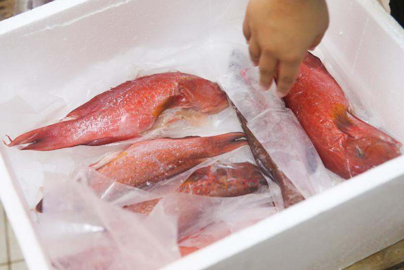 Fish which has been scaled, gutted and cleaned are packed for delivery to customers. — Picture by Choo Choy May