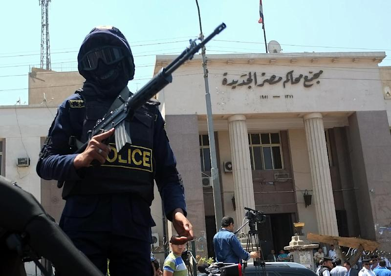 Egyptian police secure the area outside a courthouse in Cairo after a makeshift bomb exploded on June 25, 2014